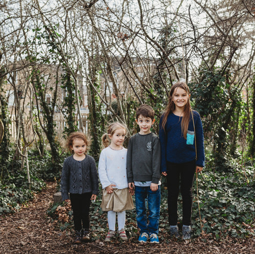Four siblings lined up in front of trees