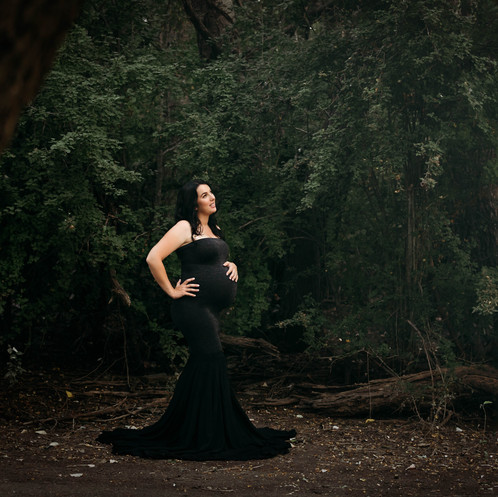 Pregant woman wearing black strapless gown posing in a dark forest