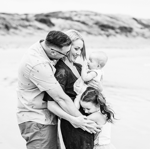 Black and white family on beach cuddling