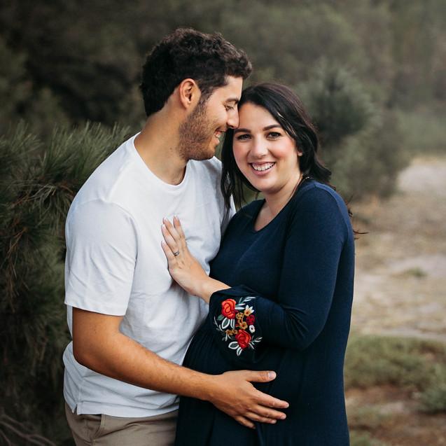 Pregannt mother cuddling loving husband and smiling