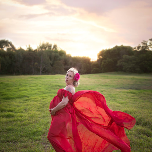 Maternity Photograph in red gown against beautiful sunset