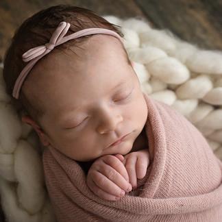 Baby girl in pink headband on handmade blanket