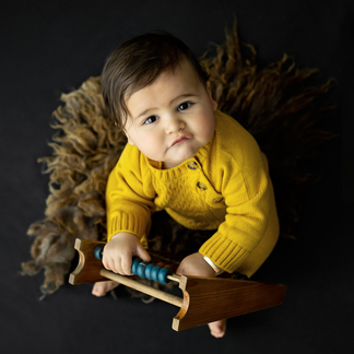 Little boy in mustard romper playing with vintage abacus
