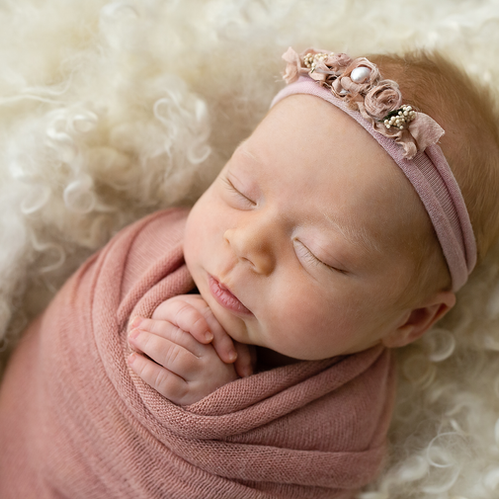 Sleeping baby girl in neutral organic wrap and blanket