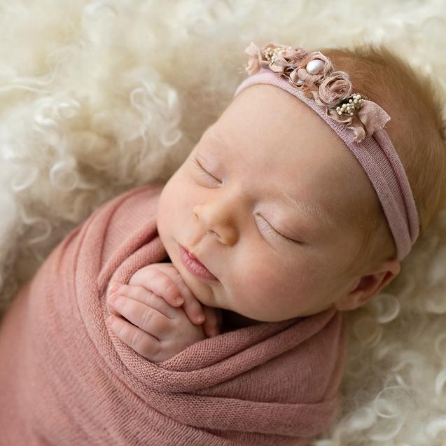 Sleeping baby girl in neutral organic wrap and blanket