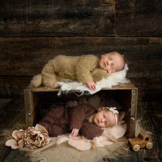 Boy girl twins fast asleep in crate