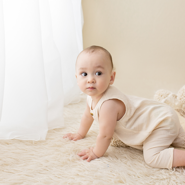 Baby boy crawling toward curtain with organic woollen layers