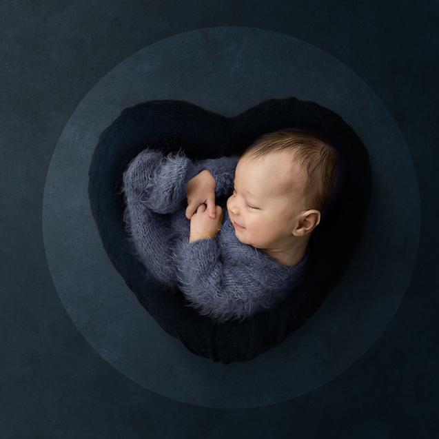Newborn baby boy sleeping in blue felt heart