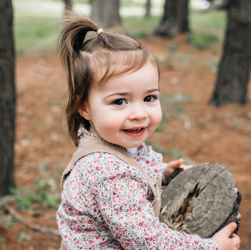 Little girl in vintage outfit holding tree stump and smiling
