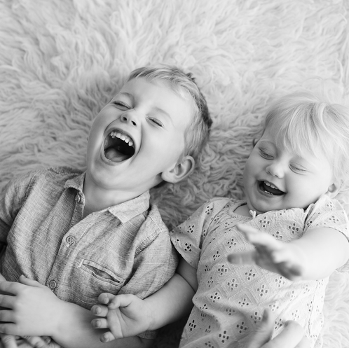 Siblings lying down and laughing in simple black and white portrait