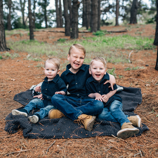Three boys laughing together sitting on blanket