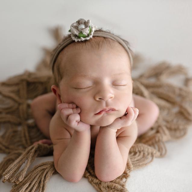Newborn baby girl sleeping in froggy pose