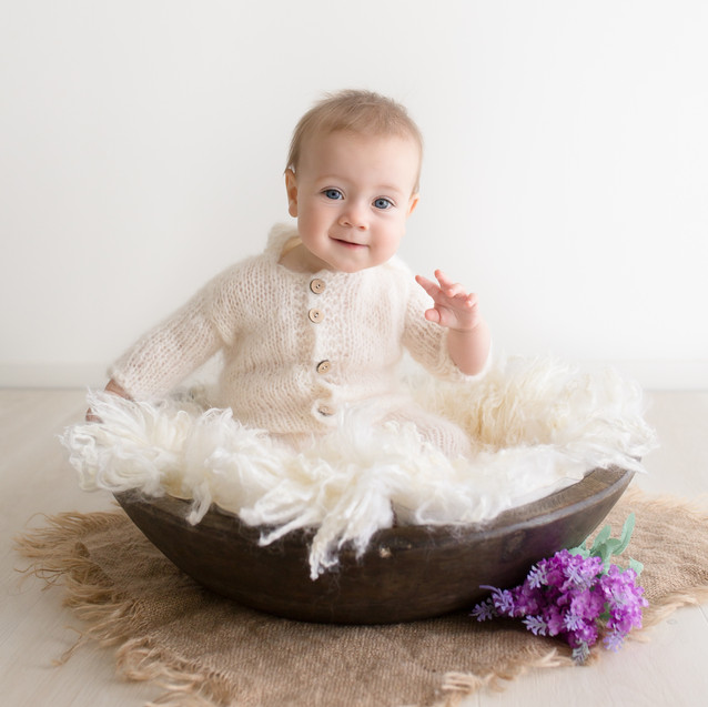 Smiling six month old baby sitting in fluffy bowl