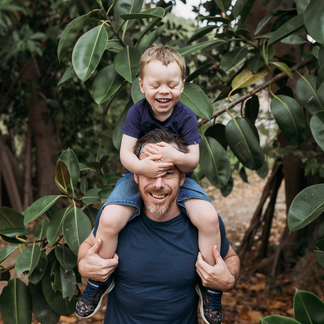 Boy sitting on Dads shoulders and covering his eyes