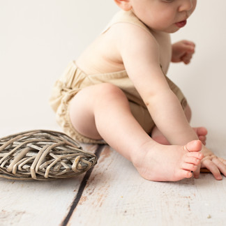 Baby sitting on timber floor with woven heart