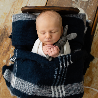 Baby boy asleep in wooden bed cuddling tiny rabbit
