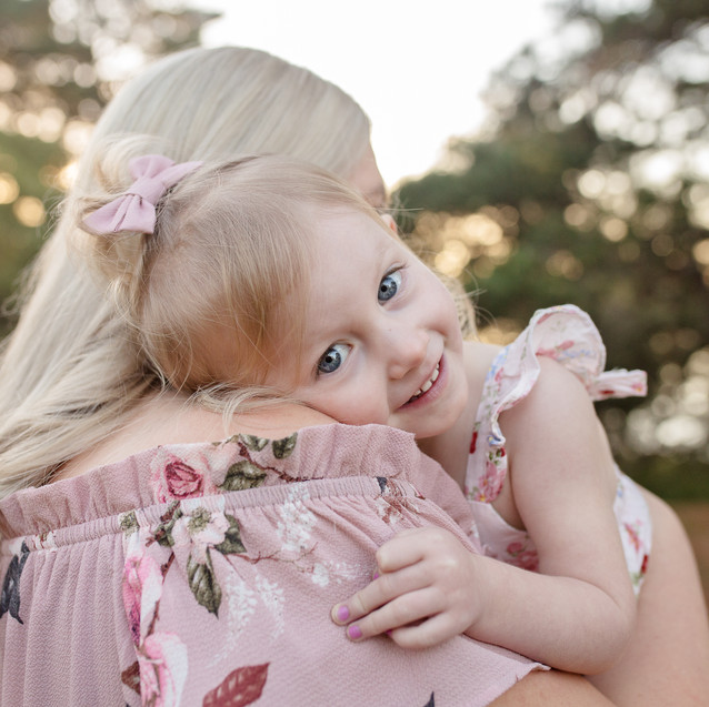 Little girl in pink looking over Mums shoulder and smiling