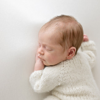 Sleeping baby in woollen romper lying on white blanket