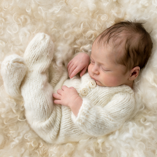 Baby girl in cream knit sleeping on curly wool