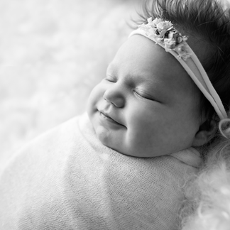 Smiling baby girl wrapped on curly wool blanket