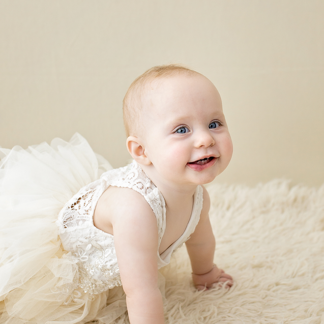 Smiling toddle in lace outfit crawling