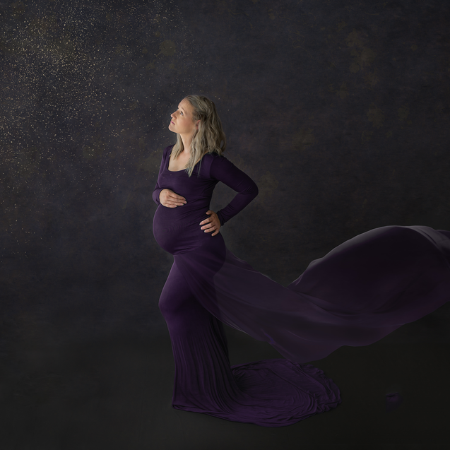 Glamourous pregnant woman in flowing purple gown