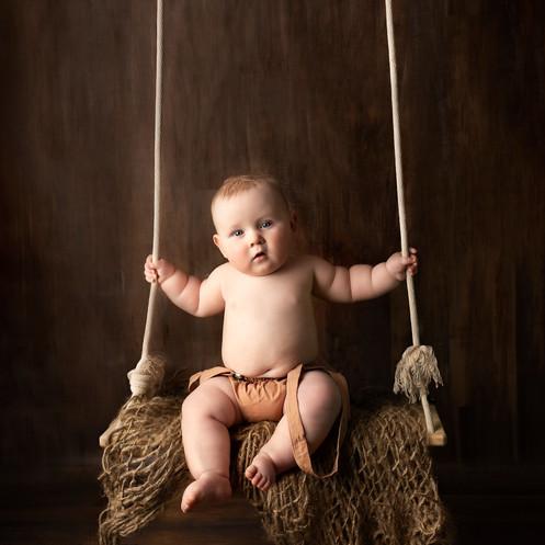 Toddler sitting on rustic swing