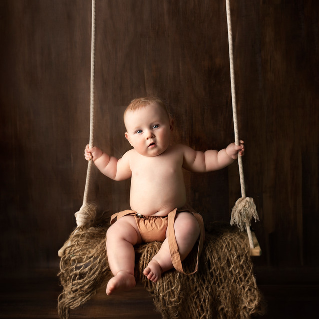 Toddler sitting on rustic swing