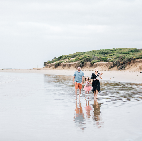 Family holiding hands and walking along beach with reflection in water