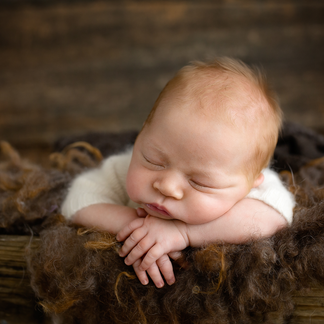 Redhead baby sleeping in timber crate