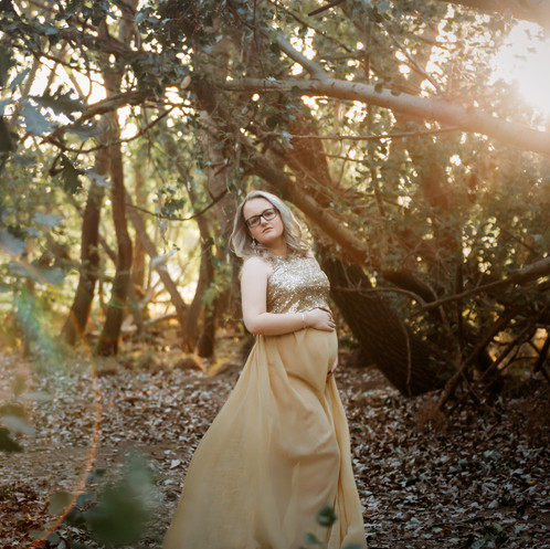 Pregnant woman wearing golden gown with golden sunlight between trees