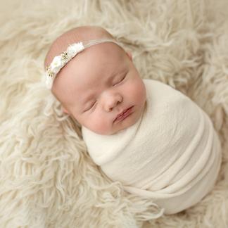 Cream wrapped baby asleep on woolen rug