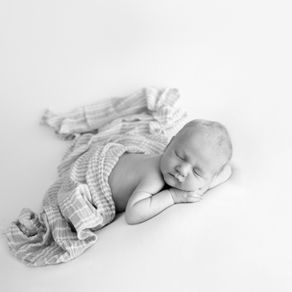 Simple pose of sleeping baby boy in black and white portrait
