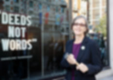 "Dr. Helen Pankhurst outside Harvey Nichols, next to the quote ""Deeds not words"""