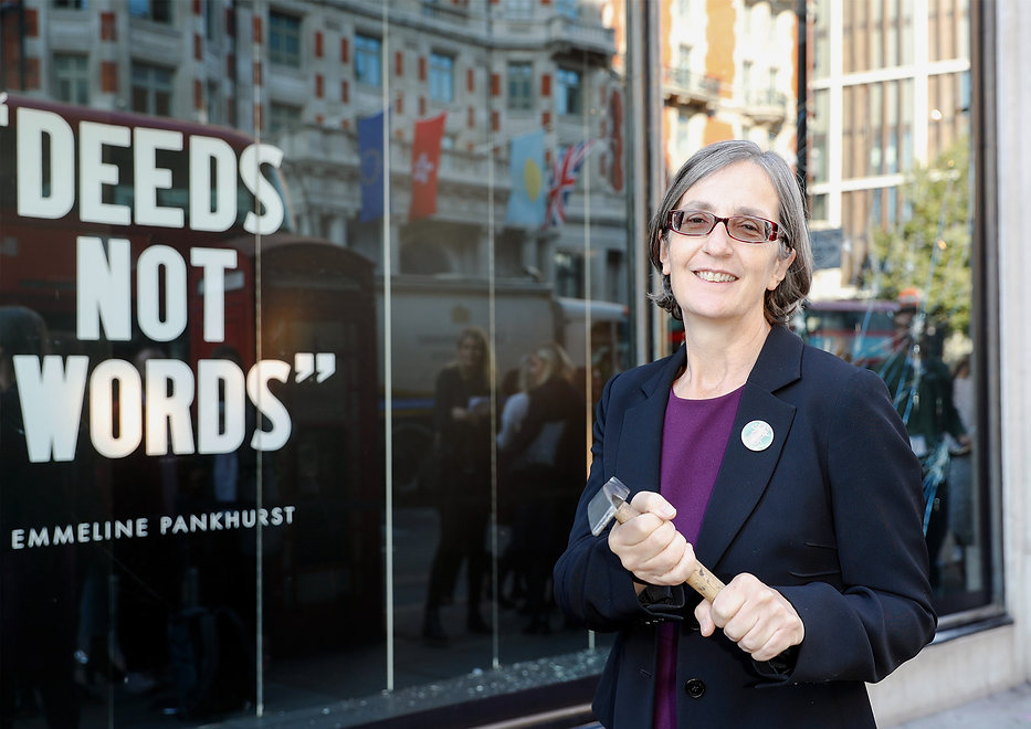 """Dr. Helen Pankhurst outside Harvey Nichols, next to the quote """"Deeds not words"""""""