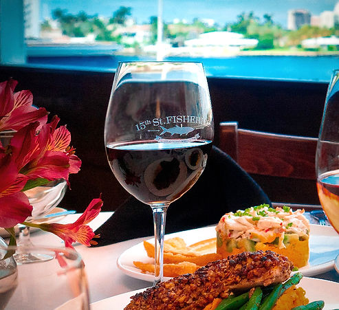 Close up view of glass of red wine and seafood specialties on a table in the dining room with waterway view in background