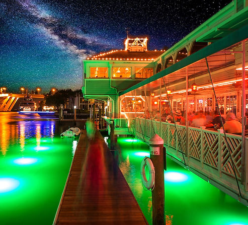 This is a glowing image of the Lauderdale Marina dock and seating area downstairs on the watefront at Fisheries Dockside.