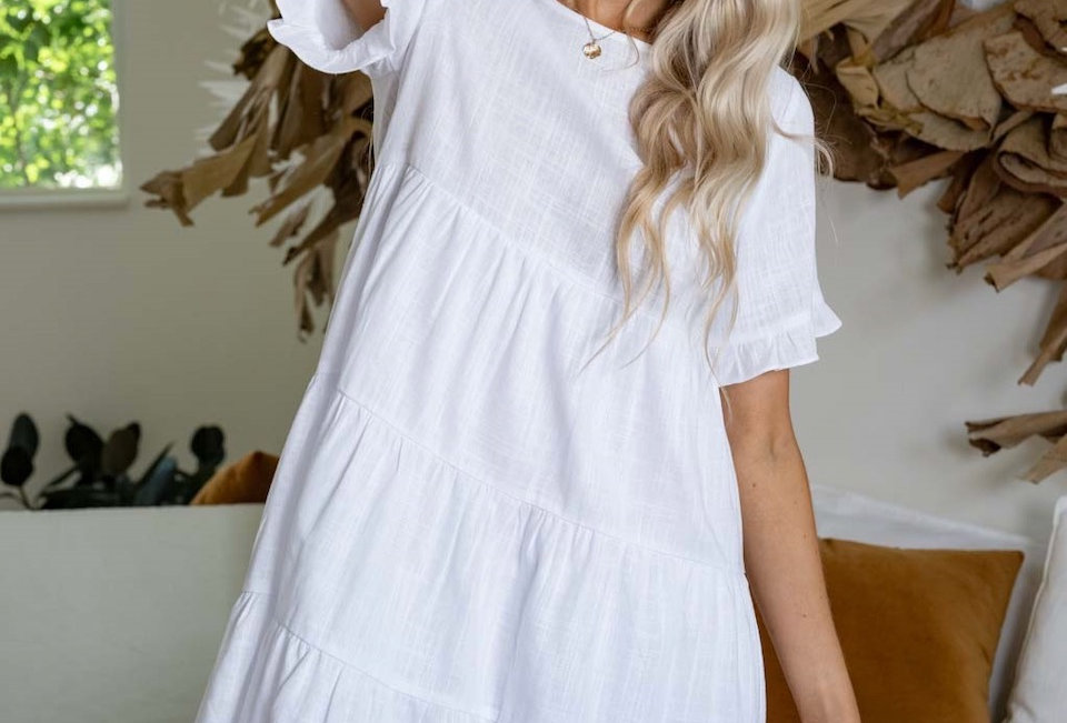 White linen mini dress, smock style  Smock style Easy fit Wooden buttons at back 3/4 Sleeve with frill Pannel detail