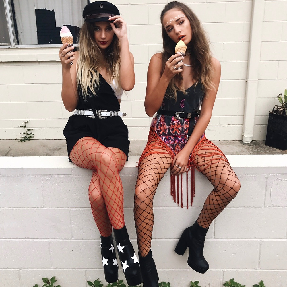 Two girls wearing tassle top, overall dress, fishnets and belts from Shine Boutiques Australia while eating ice creams