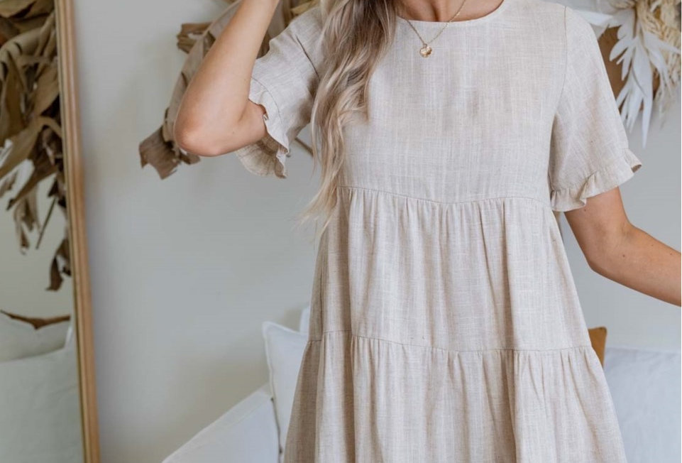 Stone colouredlinen mini dress, smock style  Smock style Easy fit Wooden buttons at back 3/4 Sleeve with frill Pannel detail