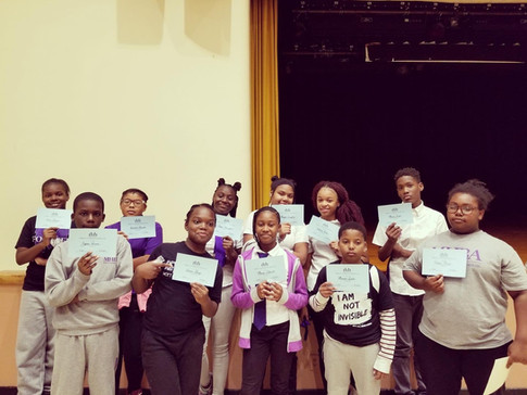 Scholars posing with awards at monthly School Assembly