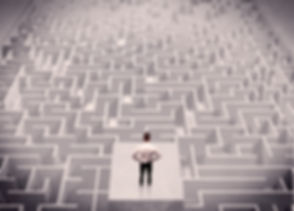 A confused businessman thinking while standing on a square platform above a detailed maze.jpg