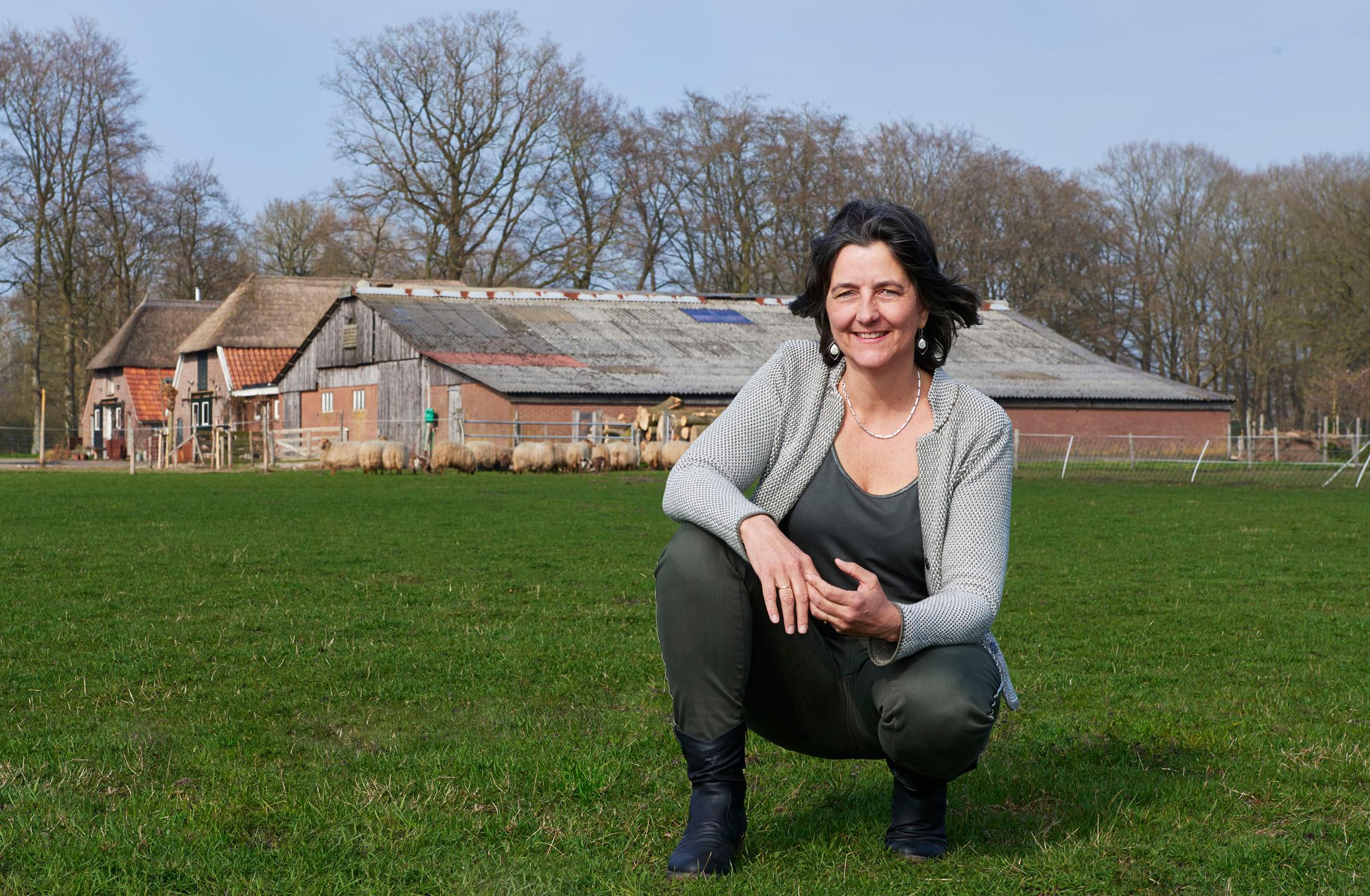 Portret van coach Paulien Boverhof van BoerenVragen met in de achtergrond een boerderij