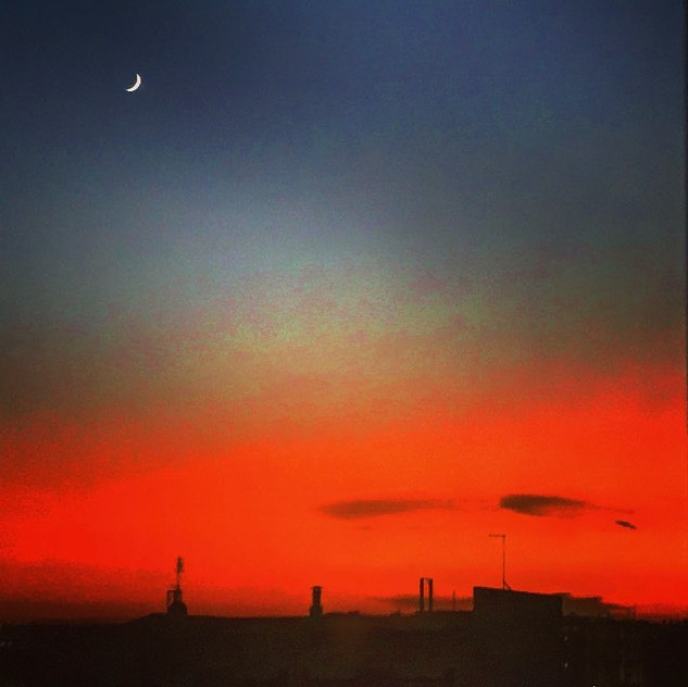 a cool jeweled moon staring at a blood red skyline (urban vision)