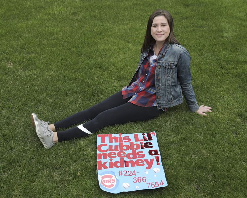 Cubs fan Bridgett Kolls, 23, sits in her front yard at home in Lombard on April 24, 2020. Kolls and her brother took a sign to a Cubs game last May to help her find a kidney donor. Due to coronavirus, her transplant surgery, scheduled for March, was postponed. (Abel Uribe / Chicago Tribune)