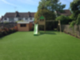 Artificial grass fake turf in garden finished install with wooden play house