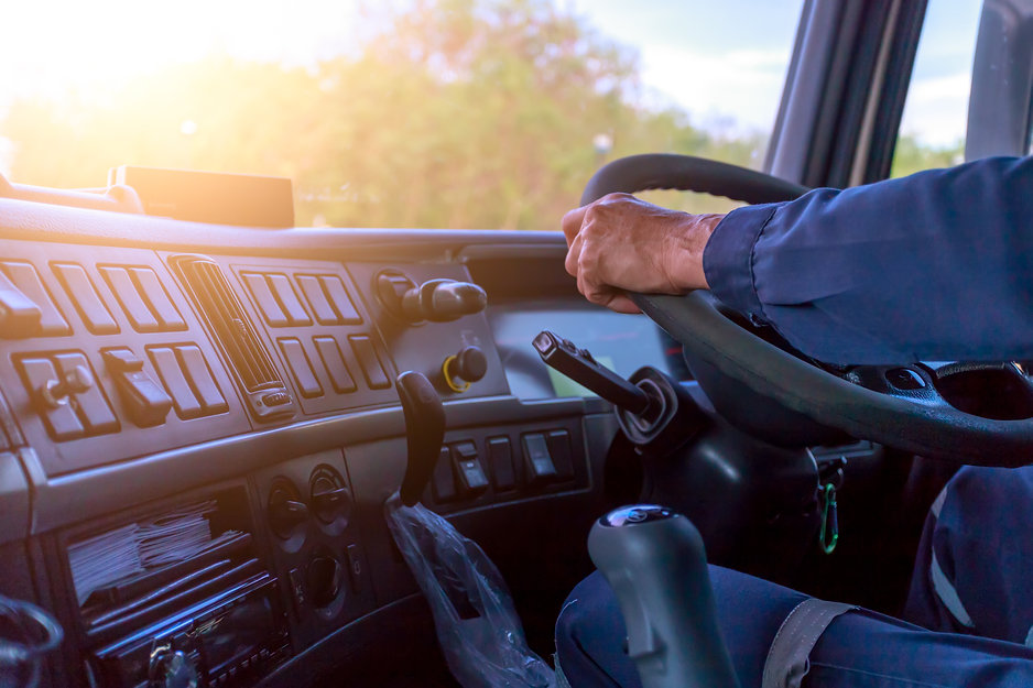 Truck driver keeps driving with hands,The man Behind Semi Truck Steering Wheel..jpg