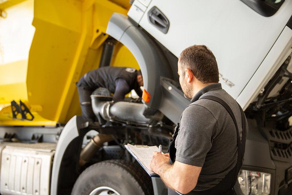 Professional technician checking truck maintenance list, truck service_.jpg