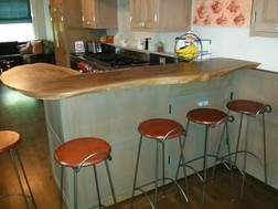 kitchen island of painted custom cabinets with wainy edged walnut counter