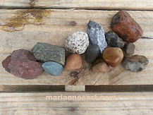 Assorted colored types of small rocks arranged on a wooden pallet